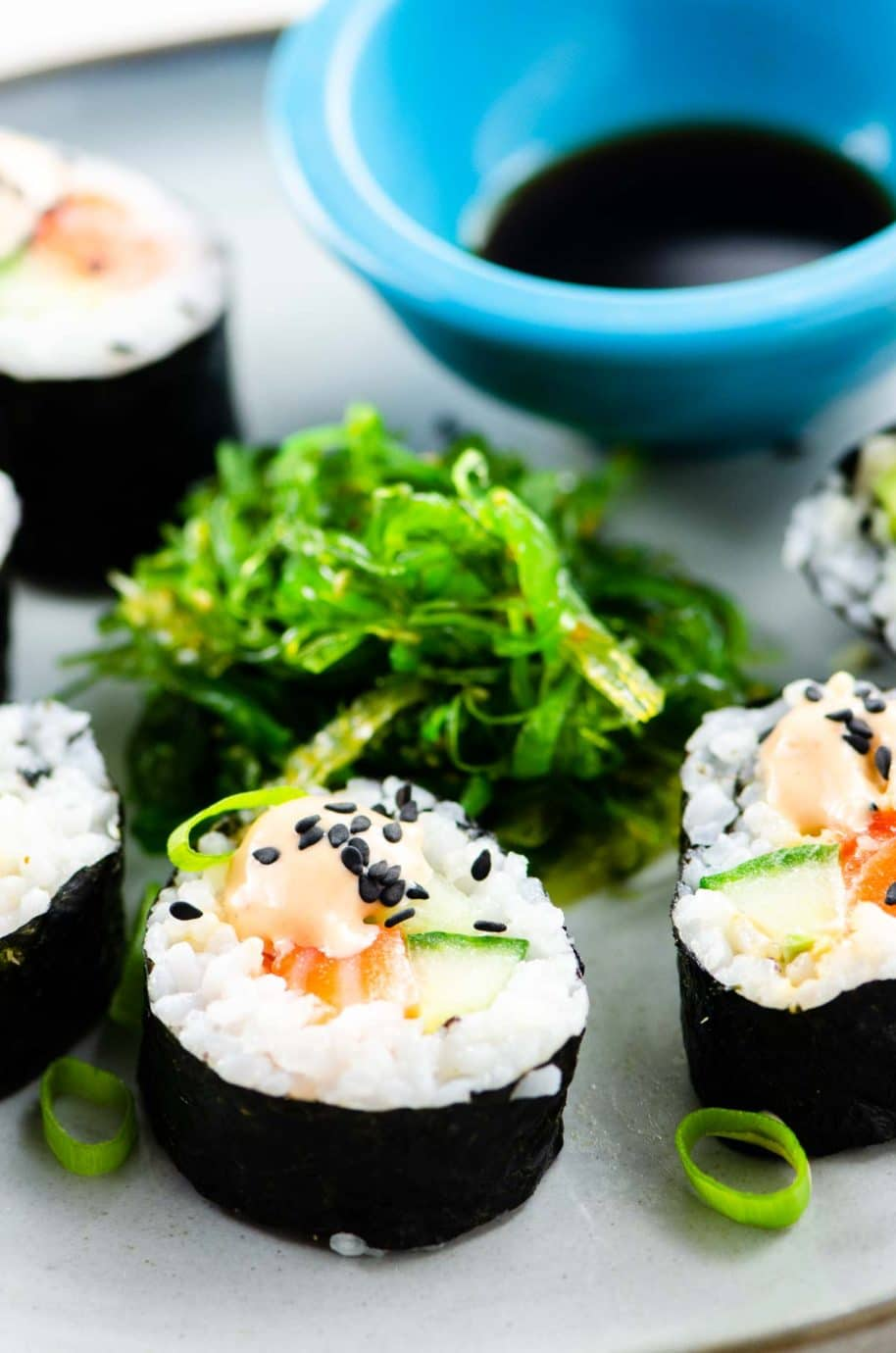 homemade sushi: spicy salmon roll, seaweed salad, and soy sauce