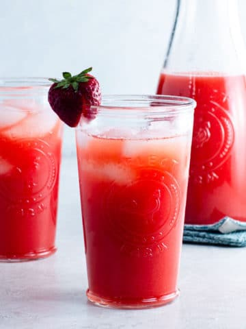 carafe and two glasses of strawberry agua fresca
