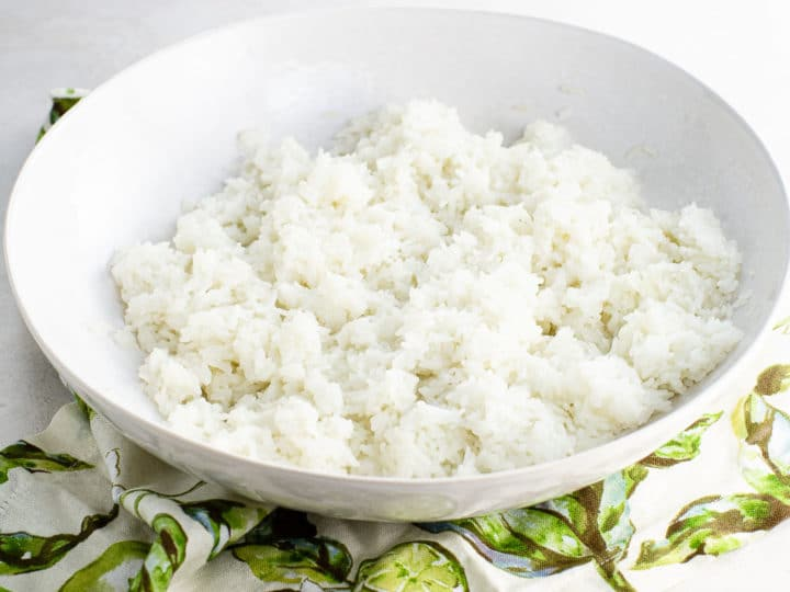 sushi rice in a shallow white bowl over a napkin