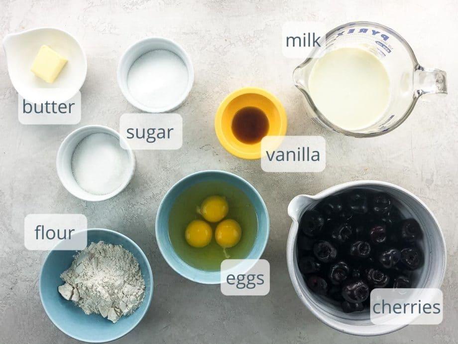 butter, sugar, flour, eggs, vanilla, milk, and cherries in bowls