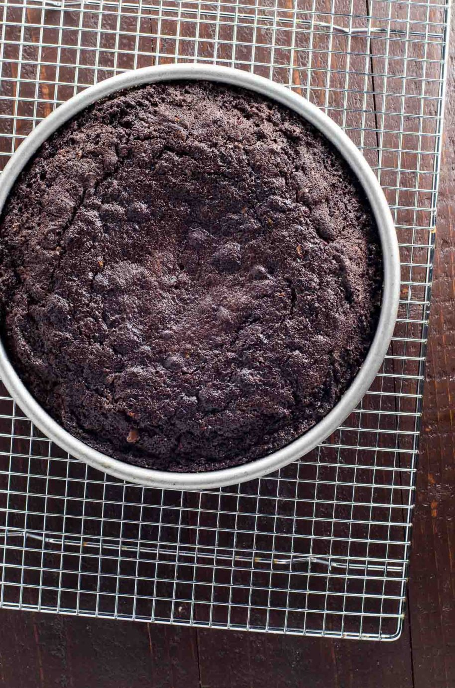 chocolate zucchini cake in a pan on a cooling rack