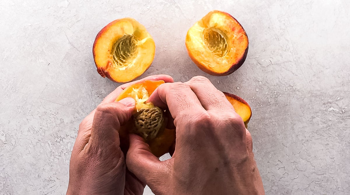 prying a pit out of a peach half