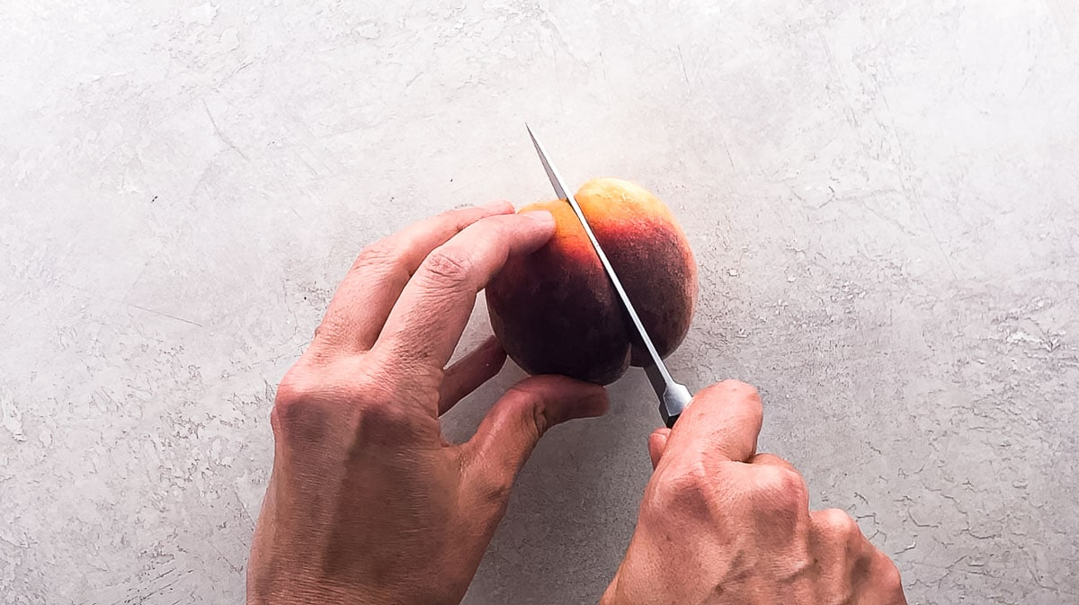 halving a peach from stem end