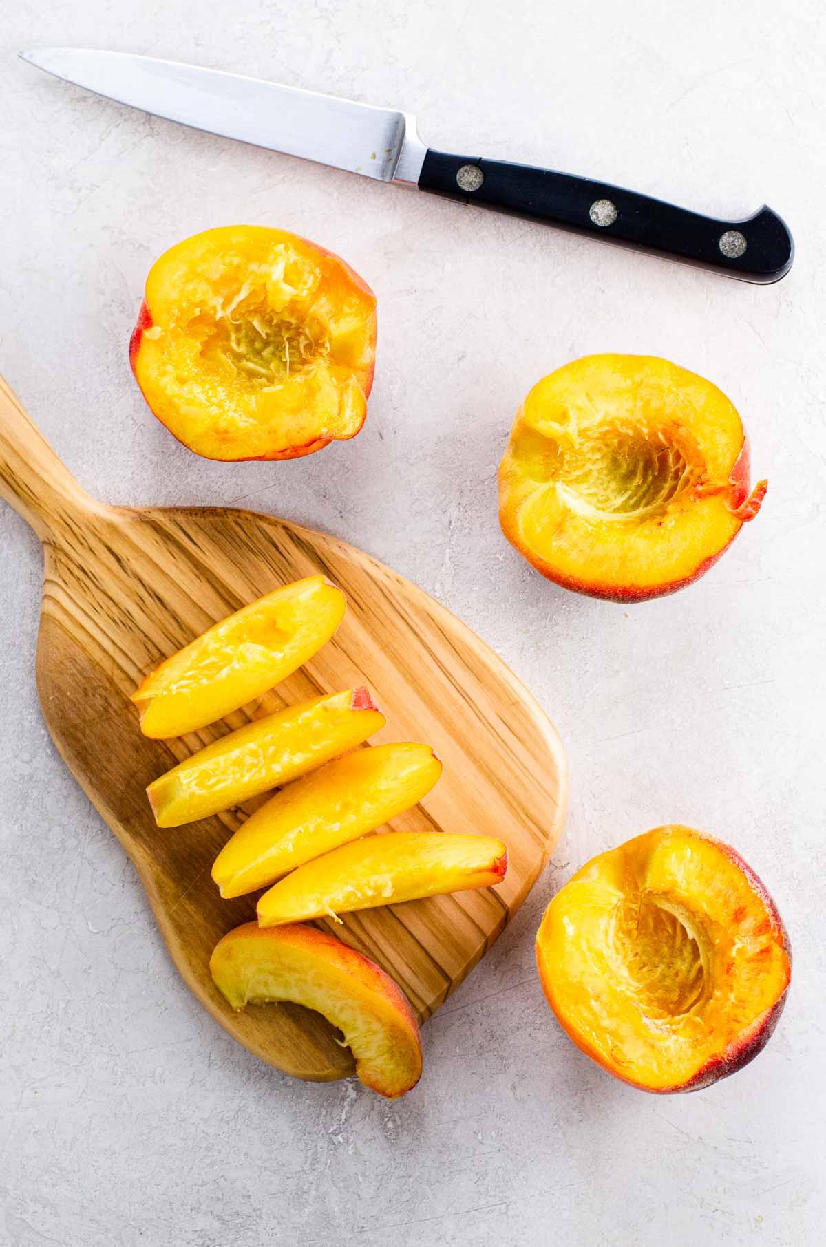 peach slices on a cutting board, peach halves, paring knife
