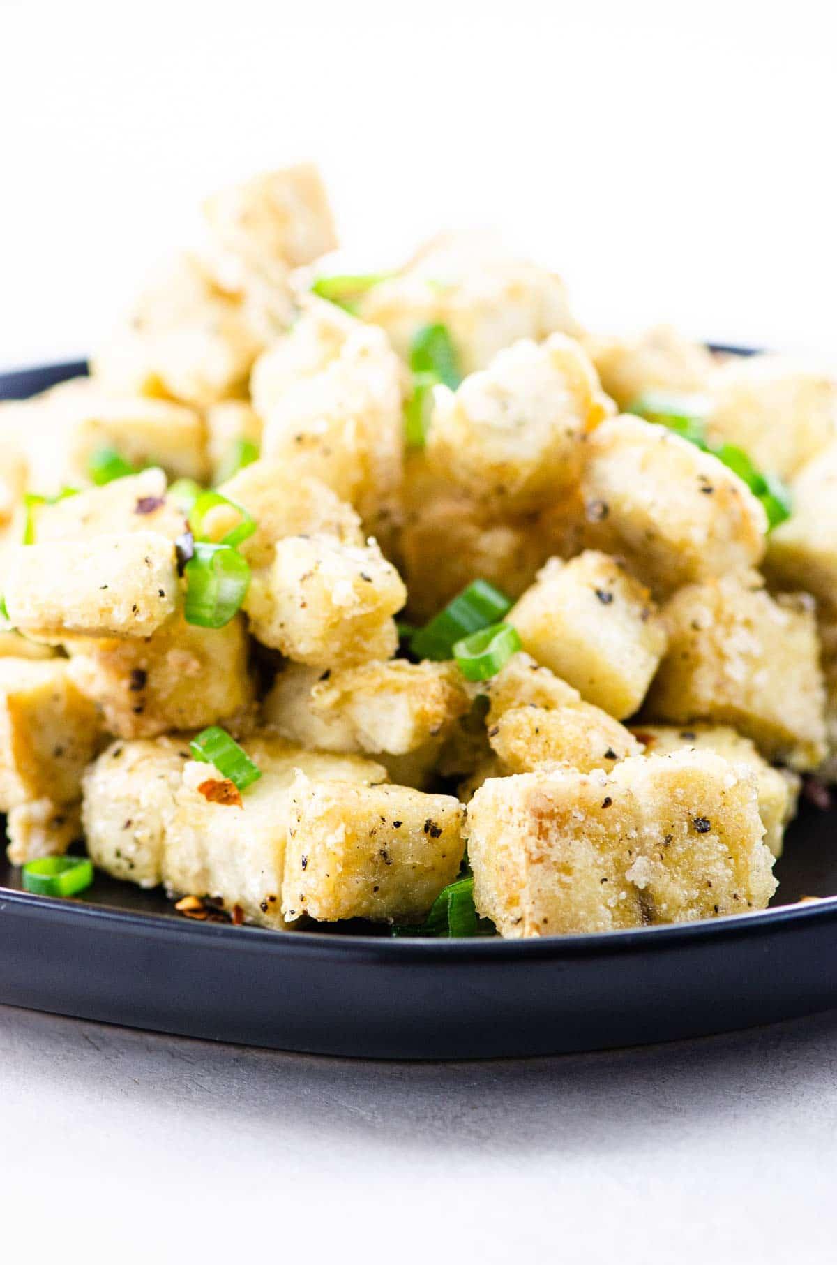 salt and pepper tofu on a black plate