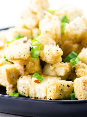 salt and pepper tofu on a black plate