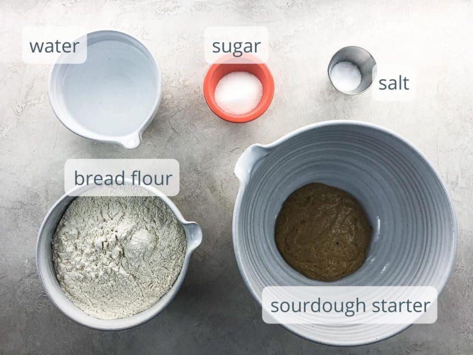 water, sugar, salt, bread flour, and sourdough starter in bowls