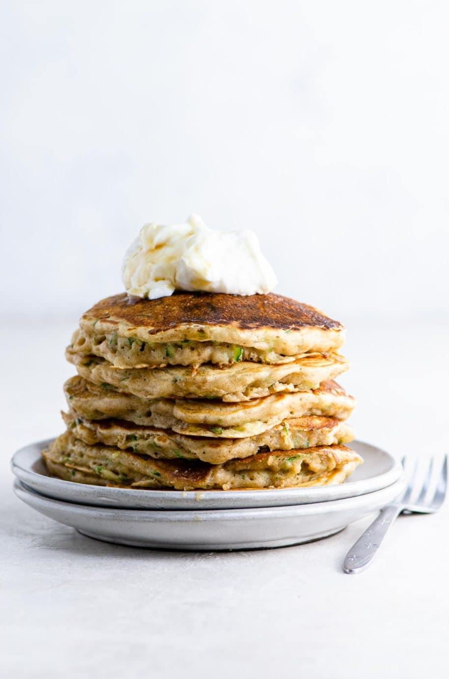 zucchini bread pancakes topped with vanilla yogurt and maple syrup