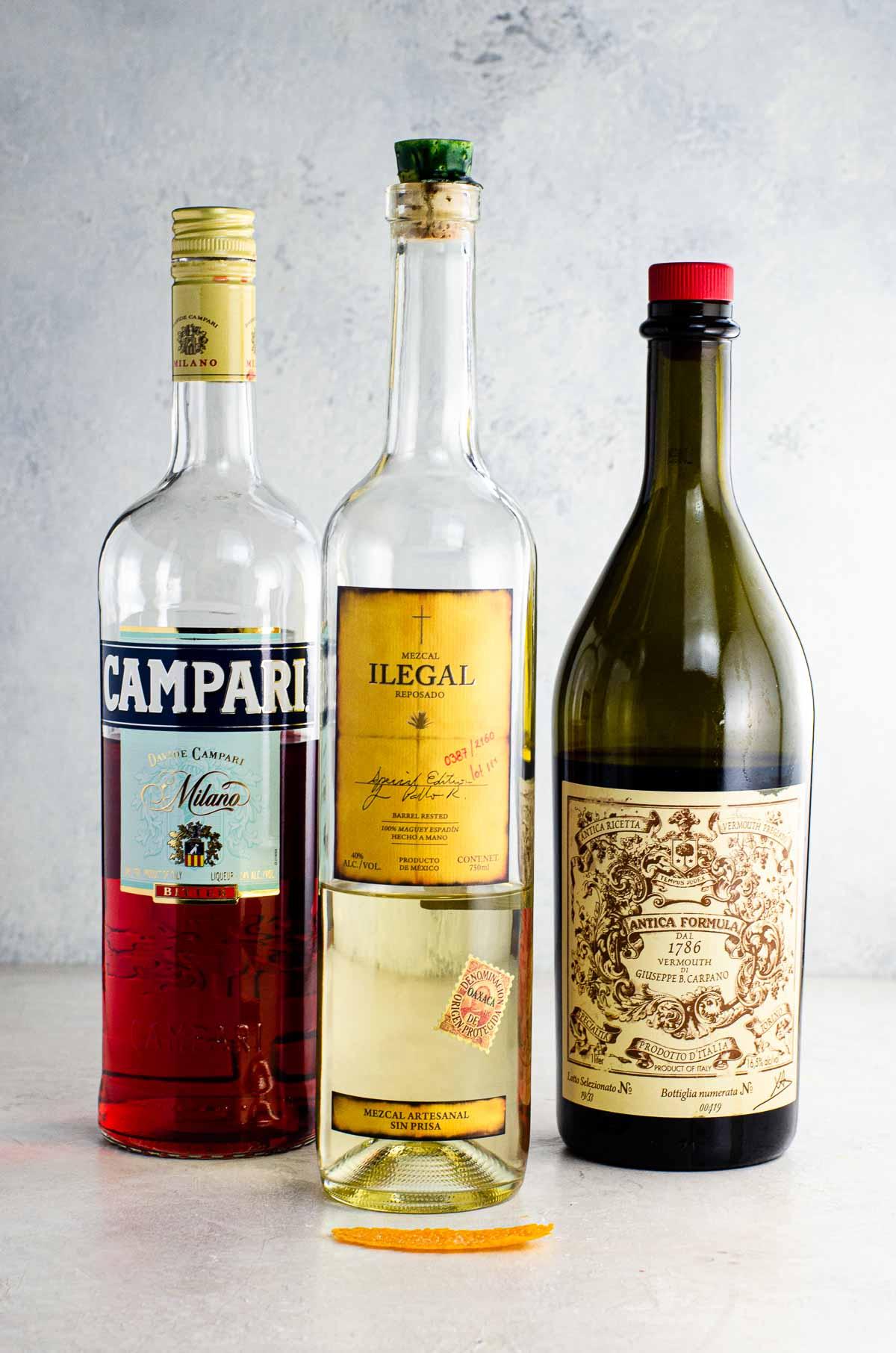 bottles of mezcal reposado, campari, and carpano anitca vermouth