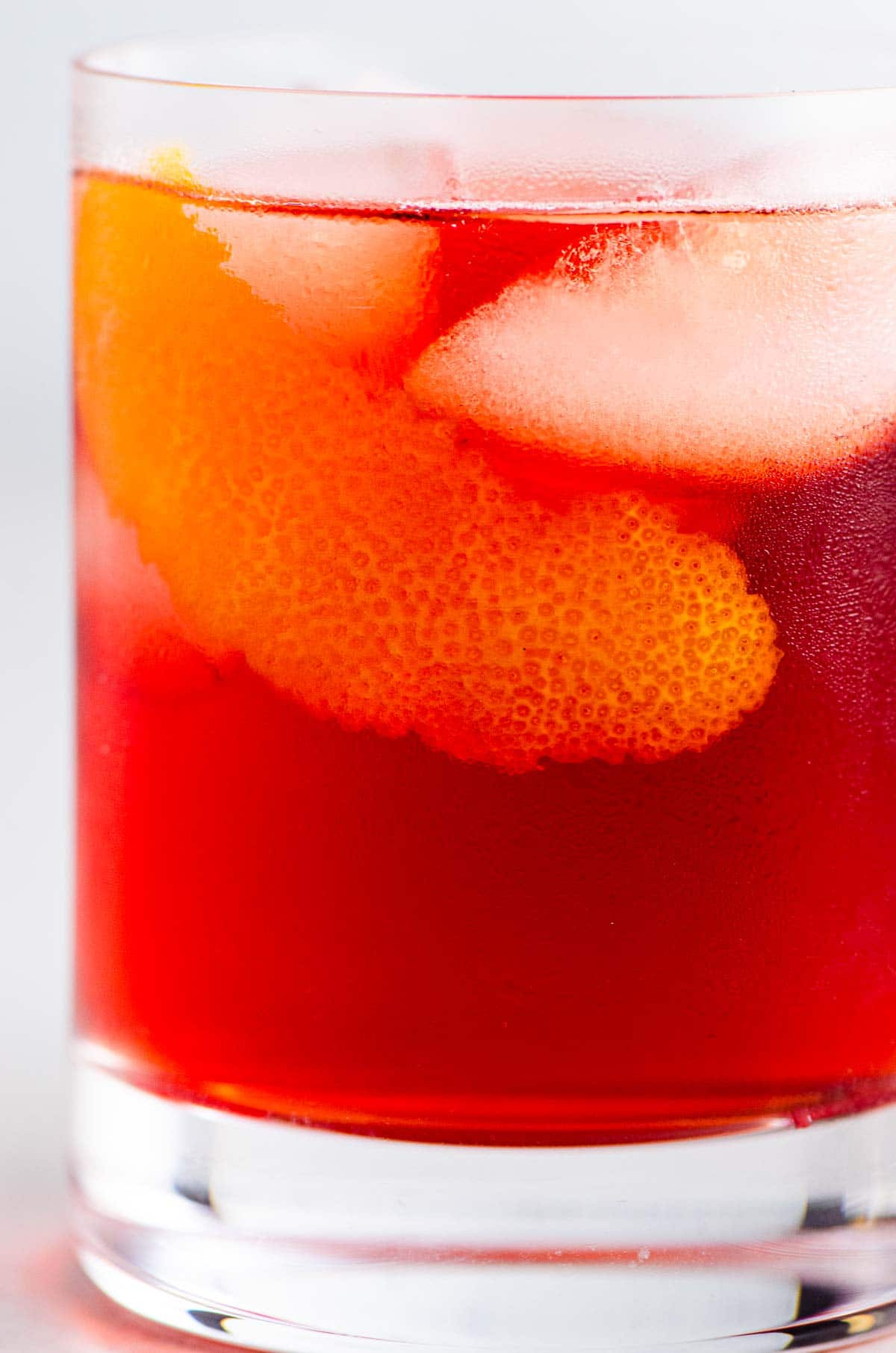 a ruby red classic cocktail with an orange twist in a single old fashioned glass