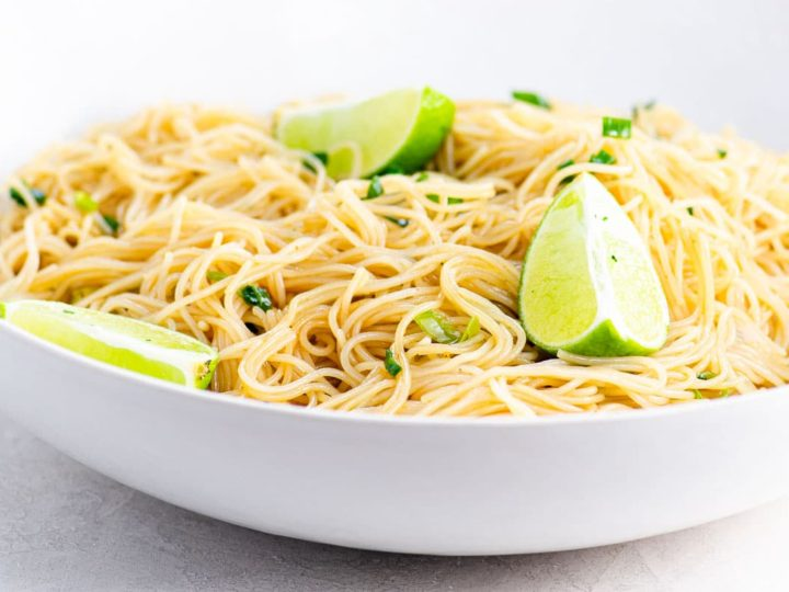 Noodles and a lime wedge on a white plate