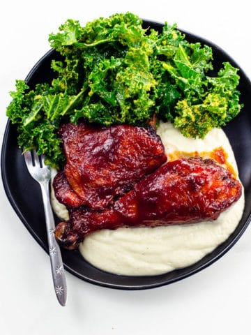 Baked BBQ Chicken Thighs and Legs on a plate with salad and cauliflower puree