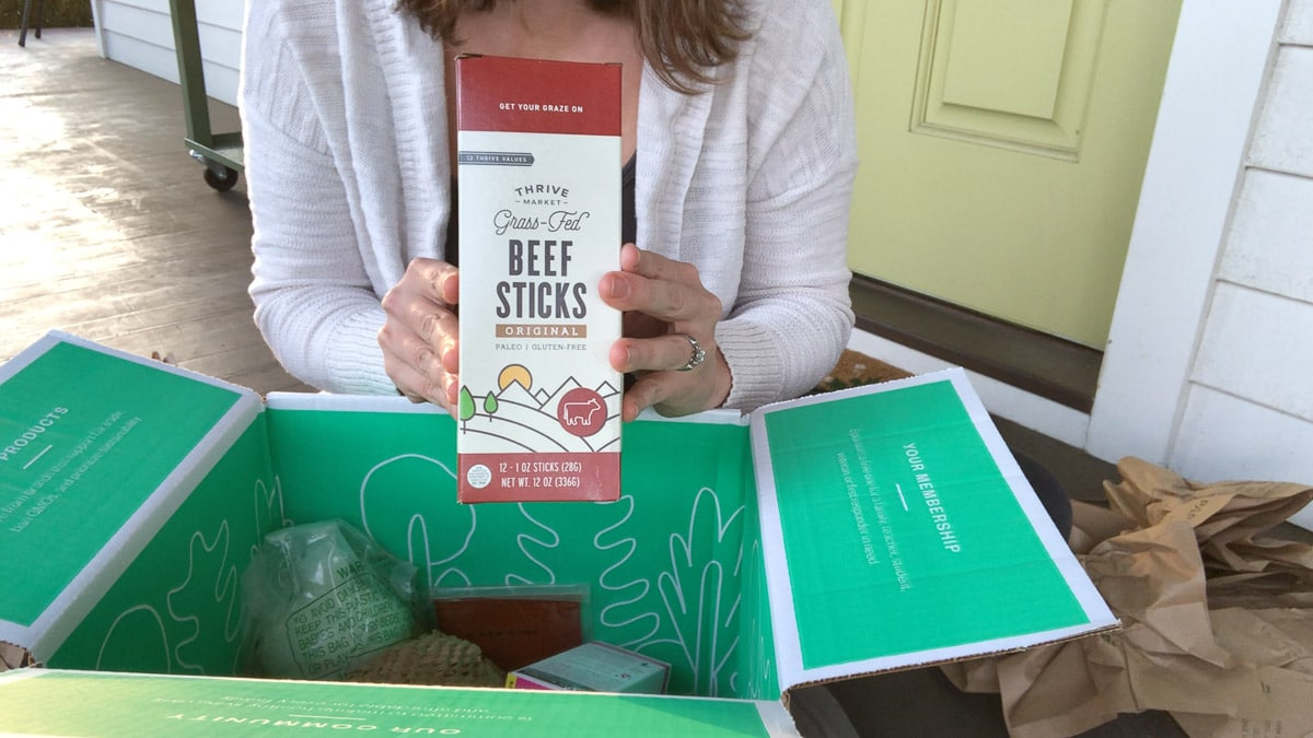 holding thrive market beef sticks over a box
