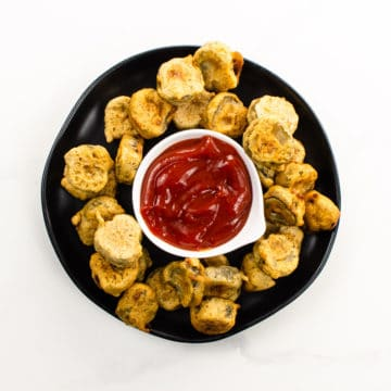 Vegan fried pickles and spicy ketchup on a black plate
