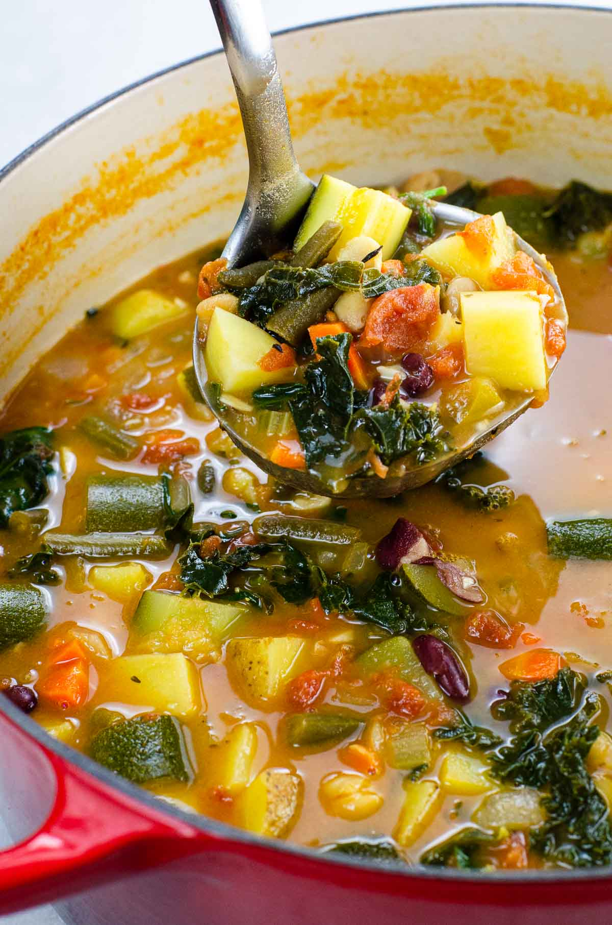 Vegan minestrone soup in a ladle and pot
