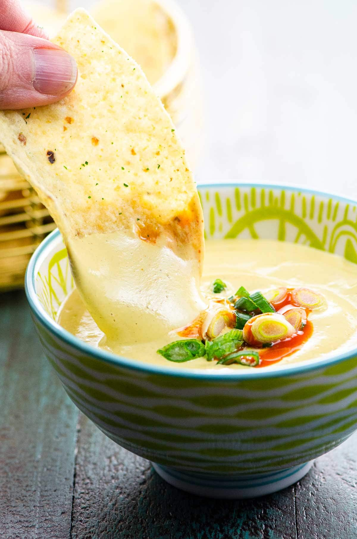 dipping into a bowl of vegan queso with tortilla chips