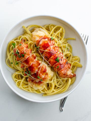 lobster poached in butter over linguine in a bowl
