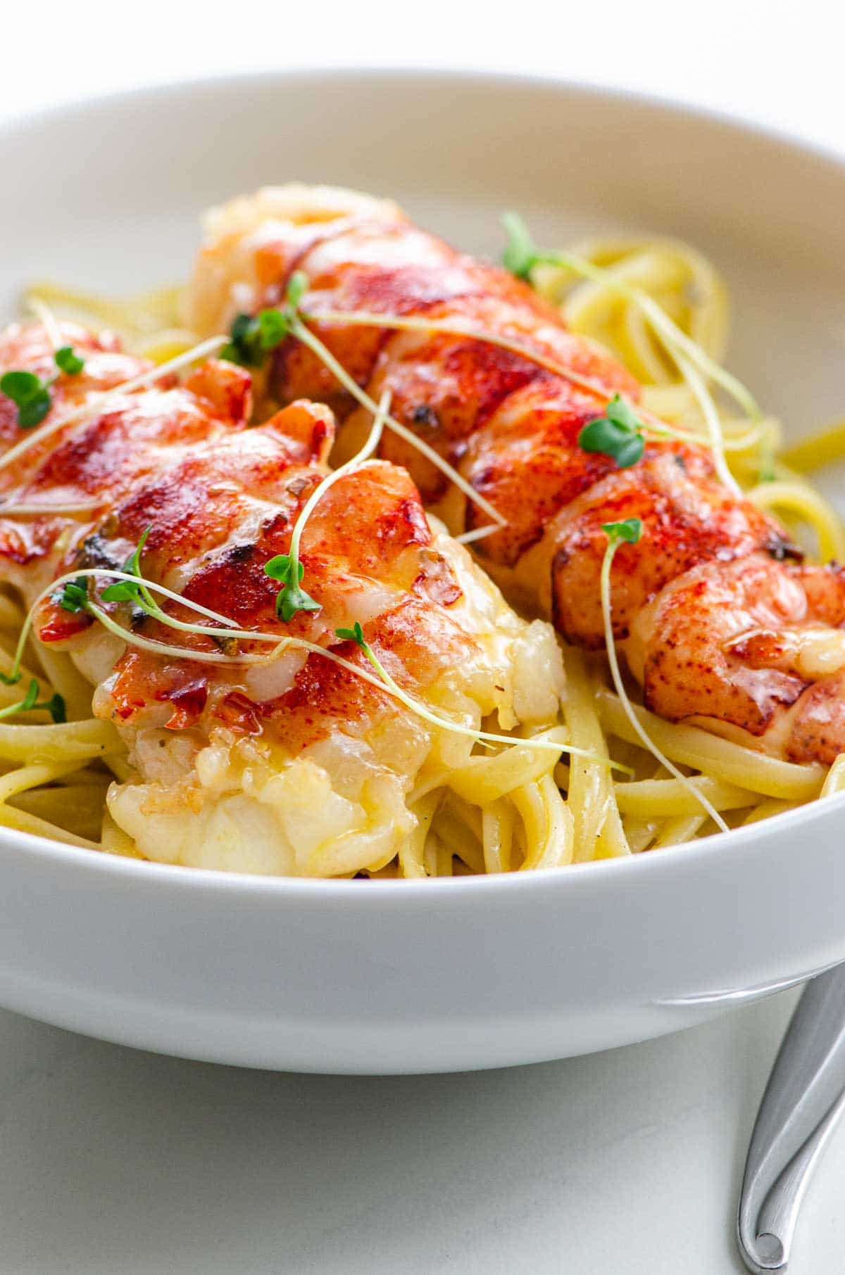 butter poached lobster tails over linguine in a bowl