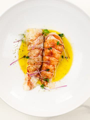 sous vide lobster tail on butter sauce in a white bowl