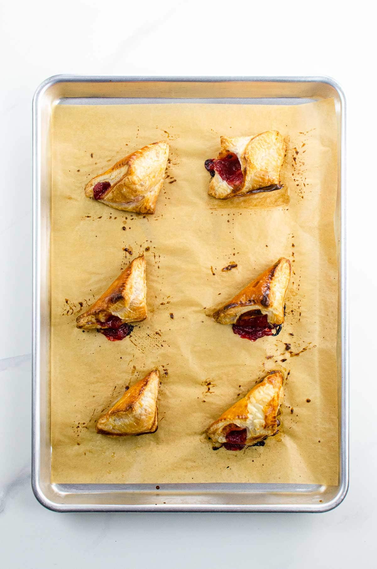 six strawberry turnovers on a sheet pan