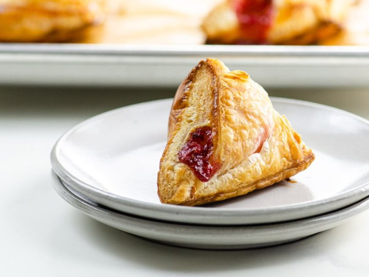 strawberry turnovers on a plate and sheet pan