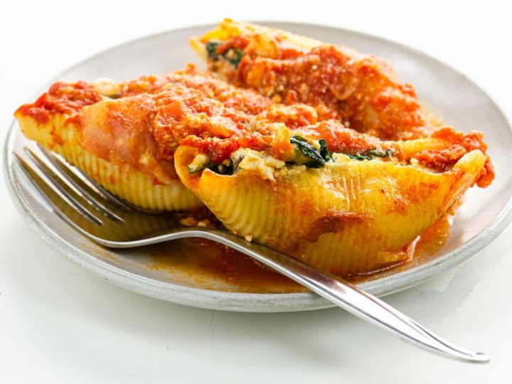 three stuffed pasta shells on a plate with a fork
