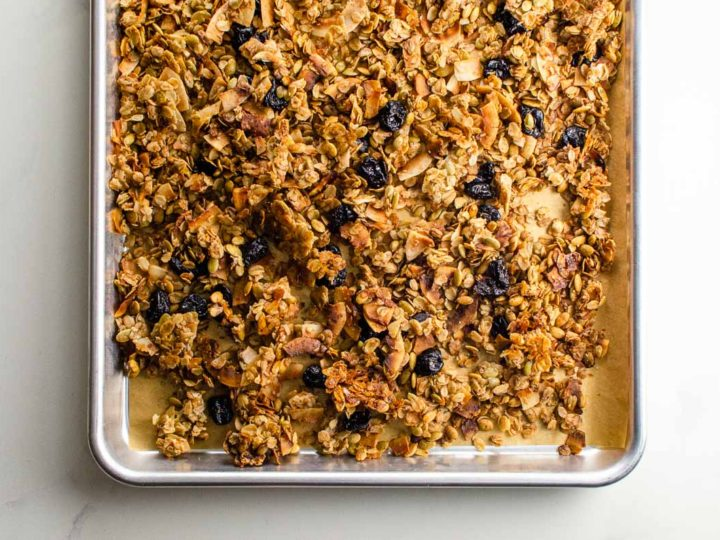 cinnamon granola with almonds, coconut, and dried cherries on a sheet pan