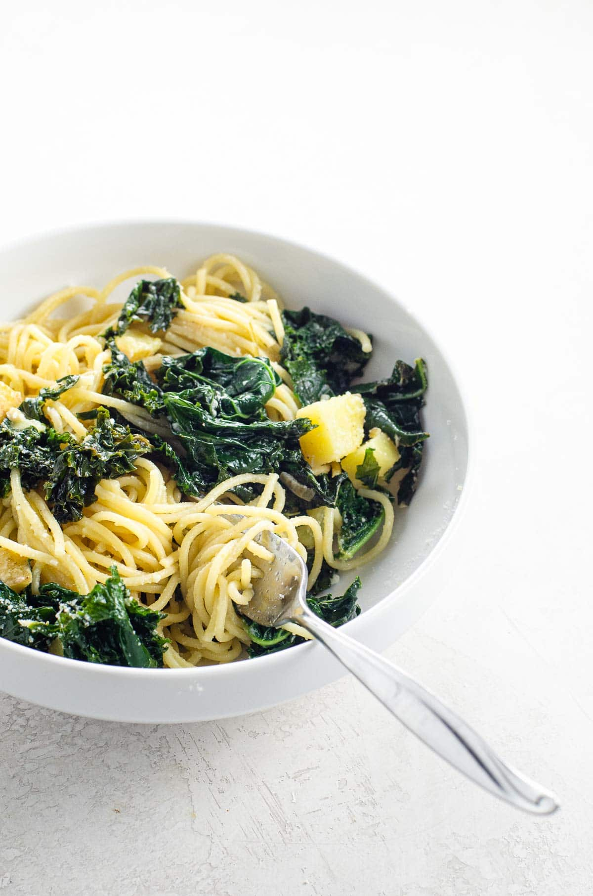 creamy kale pasta with potatoes, lemon, and capers in a white bowl
