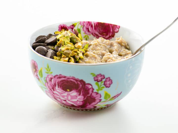 creamy oatmeal with chocolate chips and chopped pistachios in a pretty bowl