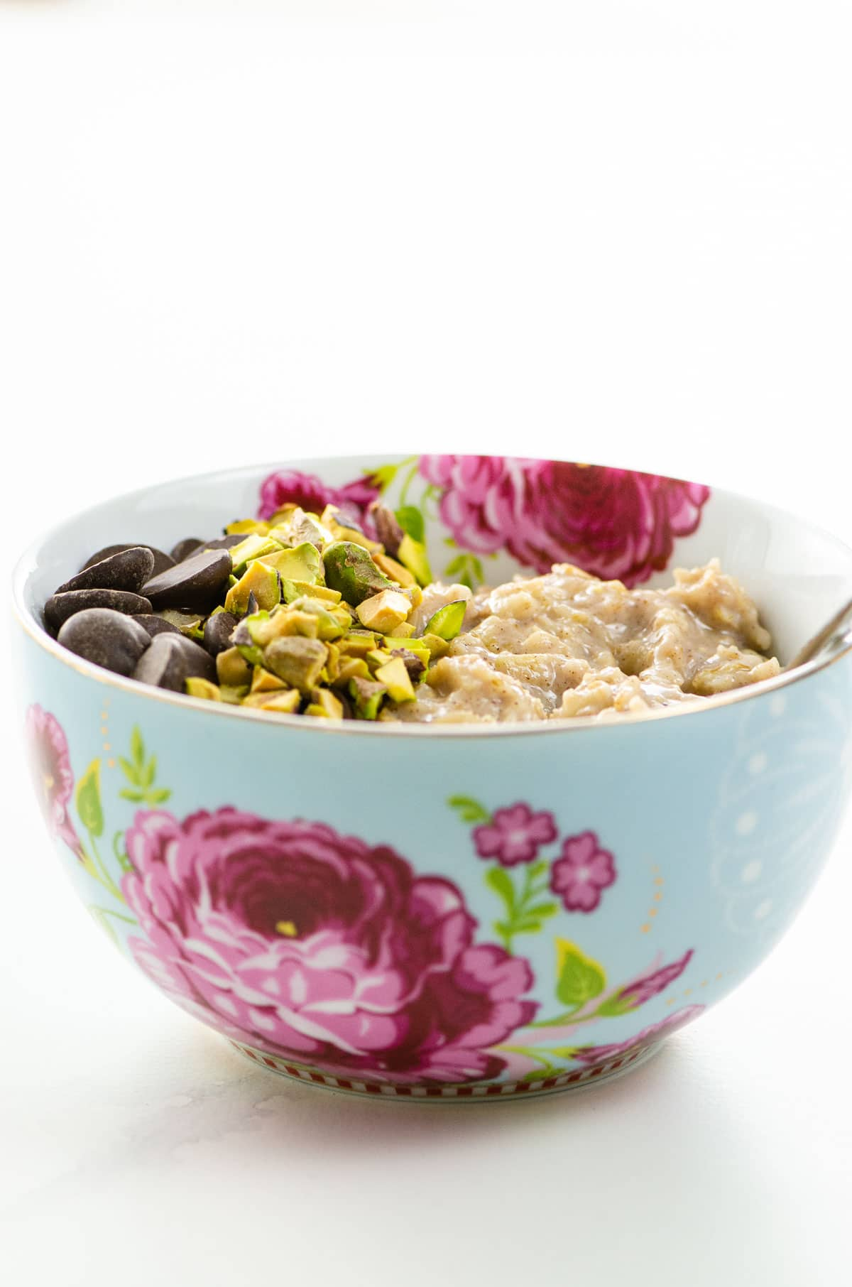 the best oatmeal recipe with chocolate chips and chopped pistachios in a pretty bowl