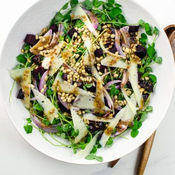 pea shoot salad with manchego, pine nuts, beets, and red onion in a white bowl