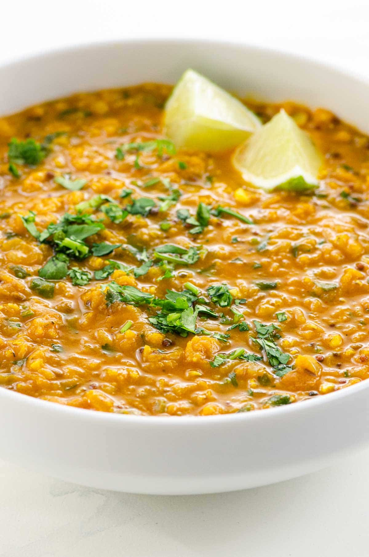 Red Lentil Dahl with Coconut Milk in a bowl with lime and cilantro garnish