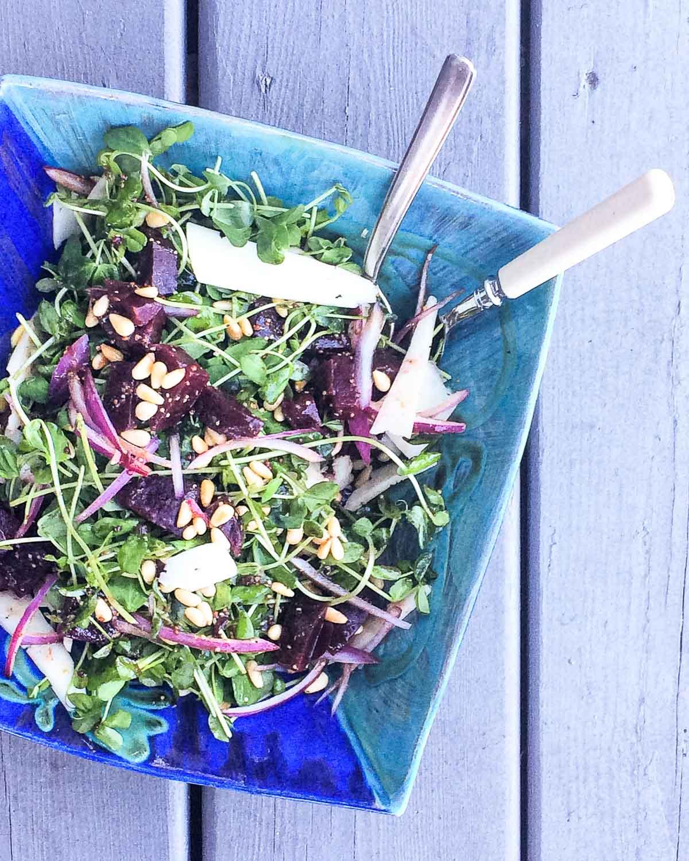 pea shoot salad on a blue plate