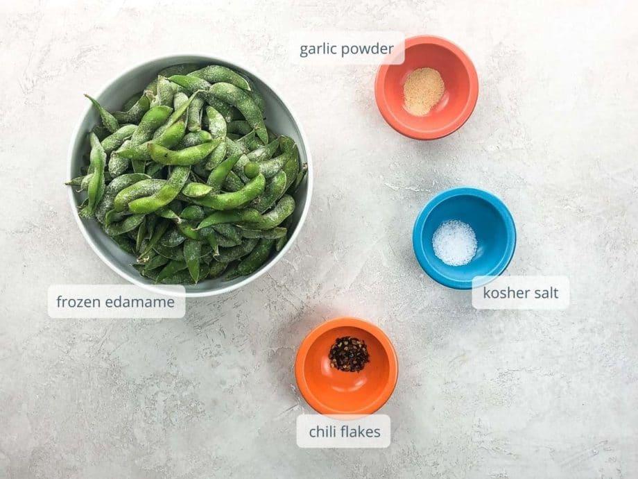 ingredients in bowls: frozen edamame, kosher salt, garlic powder, and chili flakes