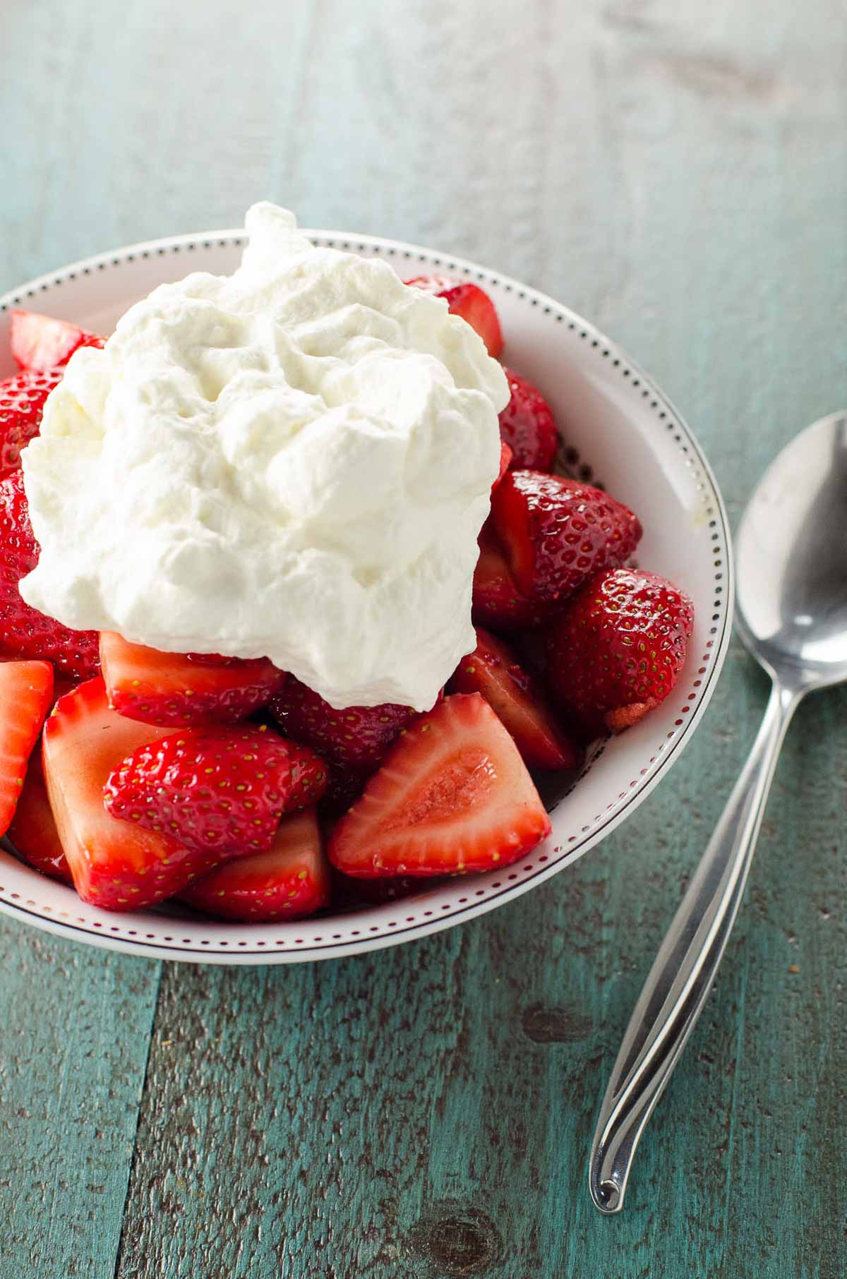 balsamic strawberries topped with whipped cream in a white bowl with a spoon on a blue background