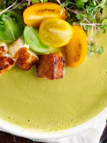 creamy asparagus ramp soup in a white bowl with halloumi, tomato, and microgreen garnish