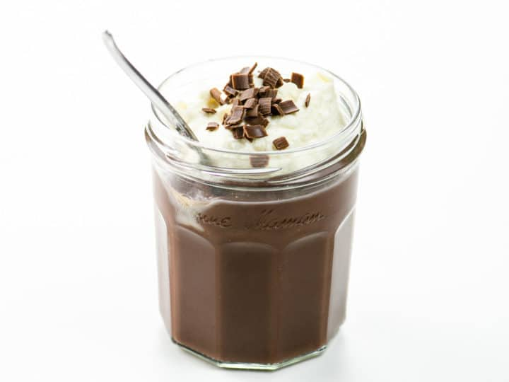 chocolate pudding with whipped cream and chocolate shavings in a jam jar with a spoon