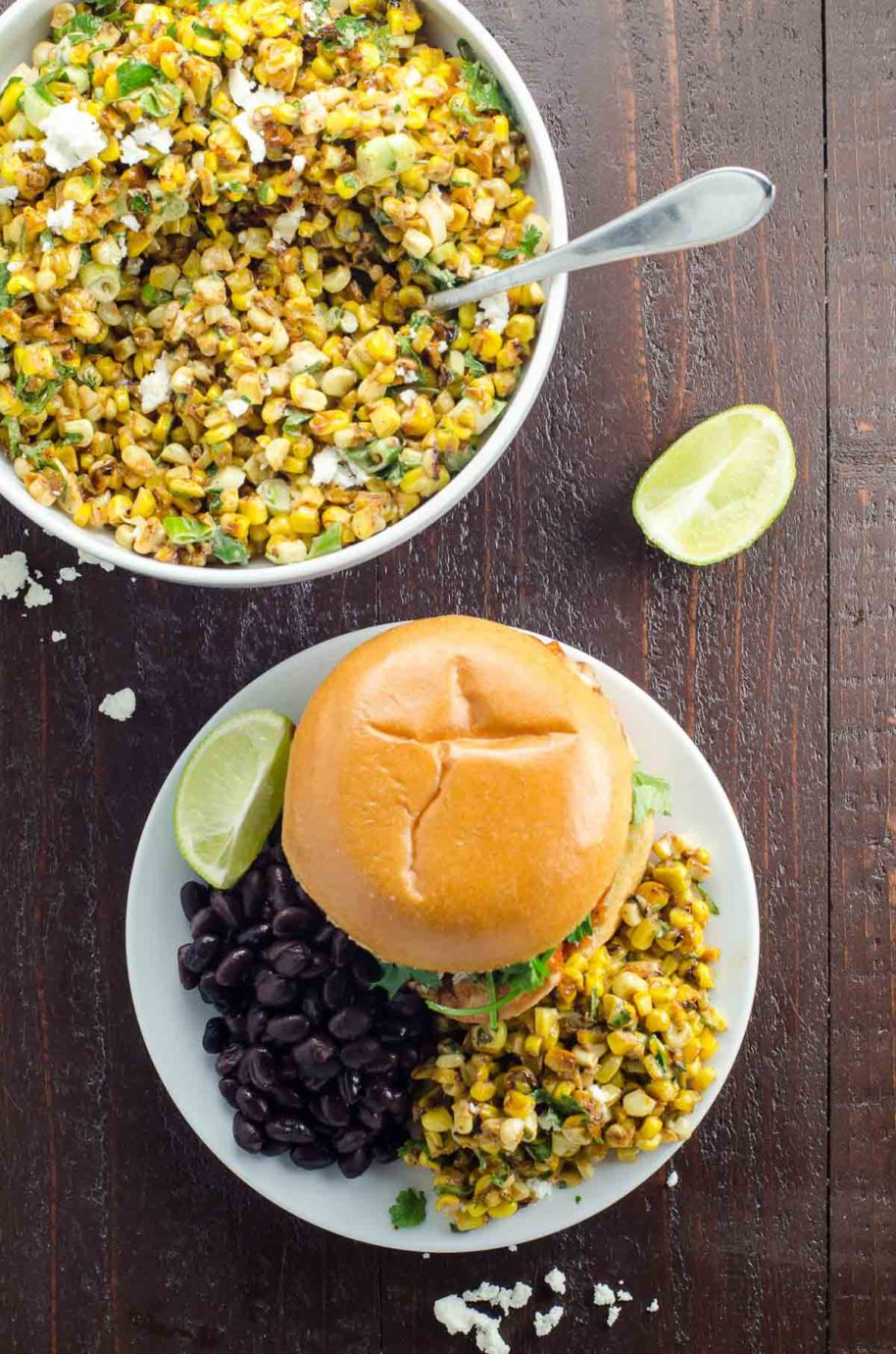 esquites (mexican street corn salad) on a plate with black beans and a sandwich