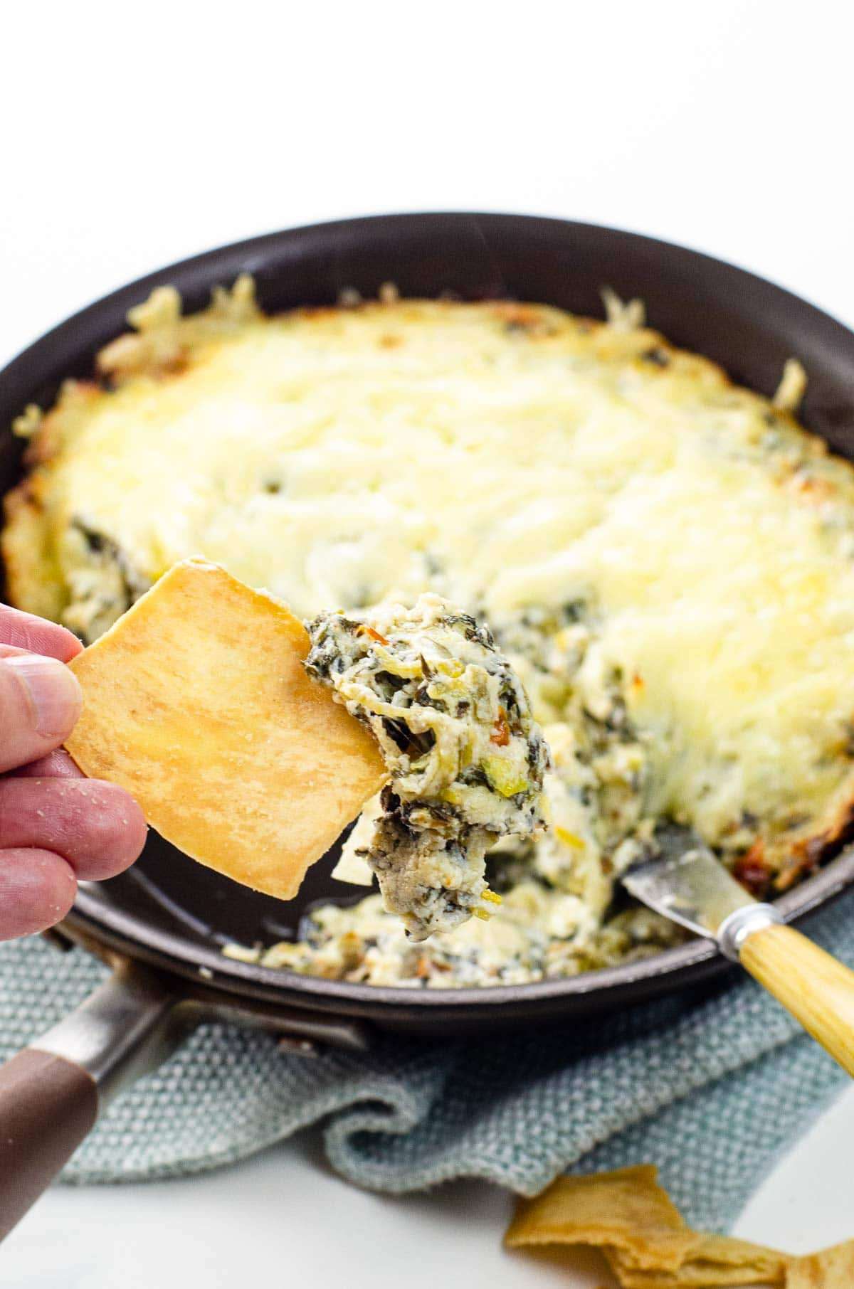 hot spinach leek dip (ramp dip) in a skillet with pita chips
