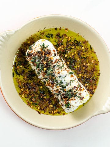 marinated goat cheese appetizer with olive oil and spices in an orange serving dish