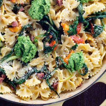 farfalle pasta with ramps, ramp pesto, cherry tomatoes, and soppressata in a pan