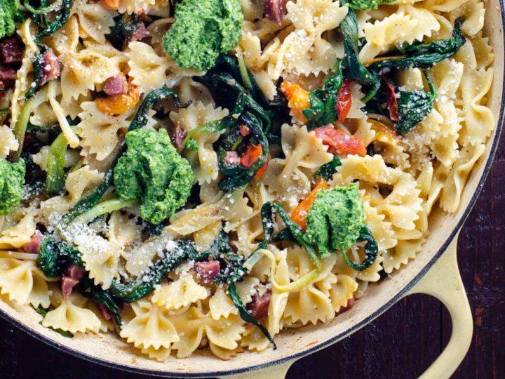 farfalle pasta with ramps, ramp pesto, cherry tomatoes, and soppressata in a pan