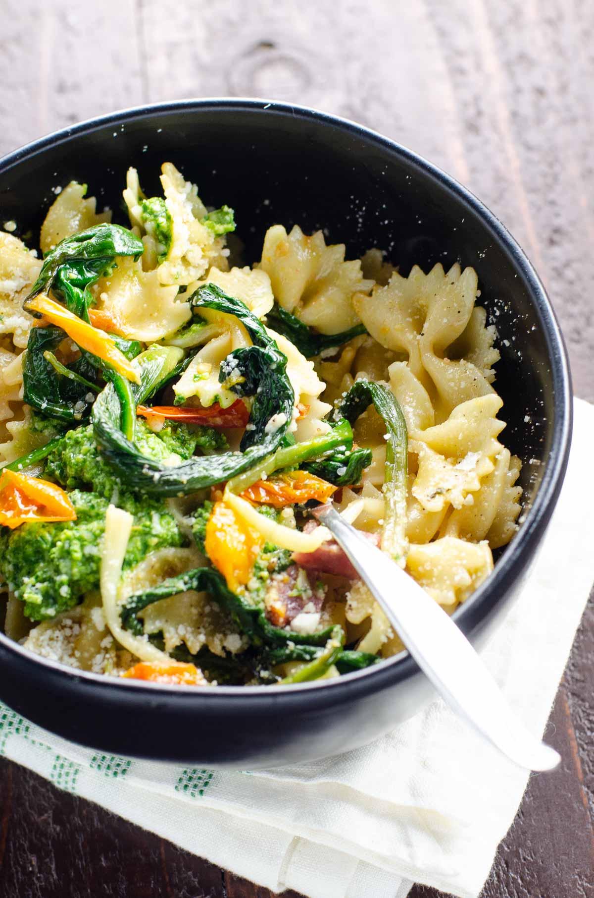 farfalle pasta with ramps, ramp pesto, cherry tomatoes, and soppressata in a black bowl