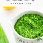 ramp pesto in a small pitcher with ramp leaves, a lemon, and pine nuts