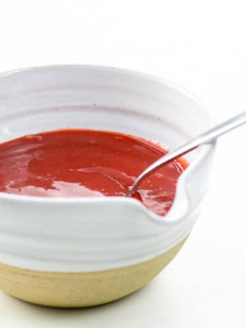 strawberry sauce for cheesecake in a bowl with a spoon