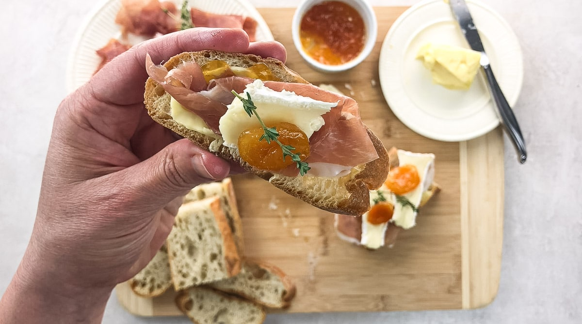Holding an appetizer-sized Prosciutto Brie and Apricot Toast