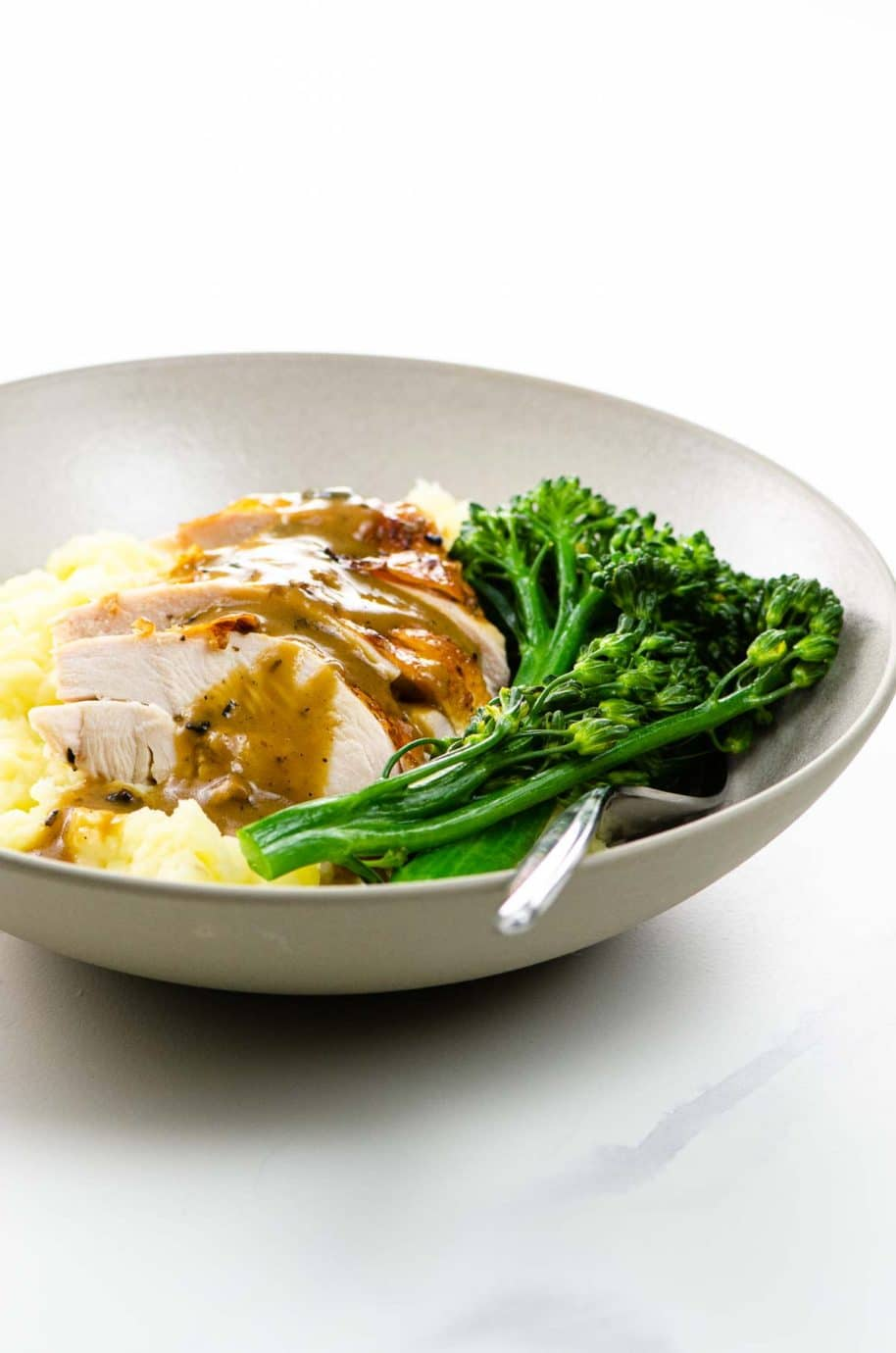 sliced spatchcock chicken breast with gravy over mashed potatoes with broccolini in a bowl