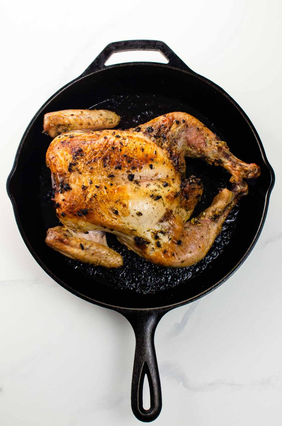 a roasted spatchcock chicken in a cast iron skillet