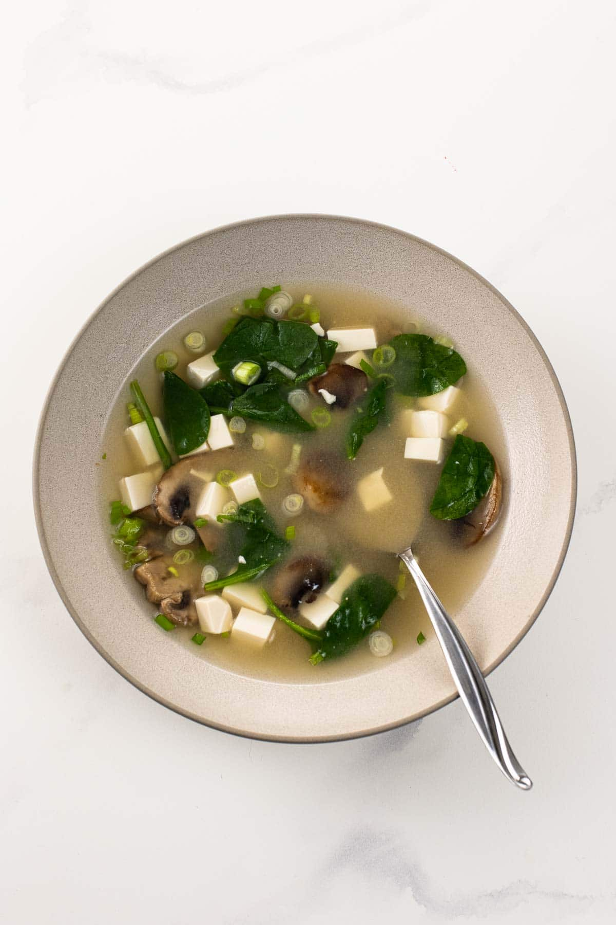 miso soup with mushrooms and spinach in a bowl with a spoon