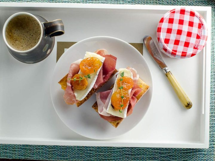 prosicutto brie and apricot toasts on a tray with coffee for mother's day breakfast in bed